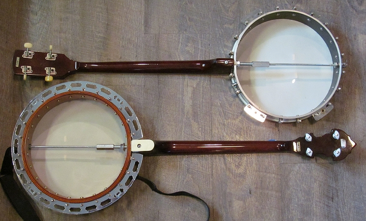 The Aria banjos with their backs off.  You can see the aluminum pot on the cheaper banjo and the multiply wooden pot on the better banjo.  You can also see that the resonator flange on the better banjo is stamped, not molded, making it only a small step up from the brackets on the cheaper banjo. Click for a 'blow-up.'
